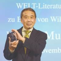 Haruki Murakami holds up the Welt Literature Prize in Berlin on Friday. | AFP-JIJI
