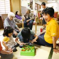 Kayoko Soman (second from right) watches kids play at Konoyubi Tomare, a day care facility for seniors, children and disabled people in the city of Toyama. | KYODO