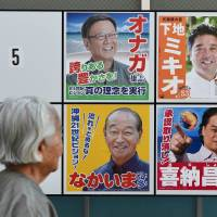 A resident of Naha, the prefectural capital of Okinawa, checks an election board featuring gubernatorial candidates in front of a polling station on Sunday. | AFP-JIJI