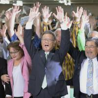 Takeshi Onaga (center), Okinawa's governor-elect, and his supporters raise their hands in a 'banzai' celebration after the former Naha mayor won Sunday's gubernatorial election. | KYODO