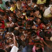 Children wait for meals to be distributed by a charitable group in a refugee area for victims of Typhoon Haiyan in Tacloban City, central Philippines, last Friday. | AP