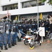 Riot police converge on Kyoto University's Kumanoryo dormitory in the city's Sakyo Ward on Thursday afternoon during a raid. | KYODO