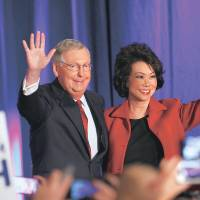 Senate Minority Leader Mitch McConnell waves to supporters with his wife, former Labor Secretary Elaine Chao, during an election-night rally on Tuesday in Louisville, Kentucky. | REUTERS