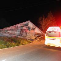 Emergency responders rush to a collapsed house in Hakuba, northern Nagano Prefecture, around 11 p.m. on Saturday night after the area was rocked by a magnitude-6.7 earthquake. | SHINANO MAINICHI SHIMBUN/KYODO