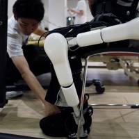 A Cyberdyne Inc. employee adjusts a Lower Limb Model HAL (Hybrid Assistive Limb) during a training session in Tsukuba, Ibaraki Prefecture, on July 22. The device can help people such as stroke victims who have partial paralysis. | REUTERS