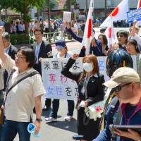 Zaitokukai Chairman Makoto Sakurai (left, with fist raised) leads an anti-Korean rally in Tokyo's Akihabara district on May 18. | KYODO