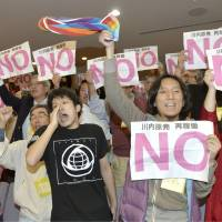 People standing in the public gallery of the Kagoshima Prefectural Assembly on Friday protest its decision to approve the restart of two reactors at the Sendai nuclear power plant. Gov. Yuichiro Ito approved the restart later the same day. | KYODO