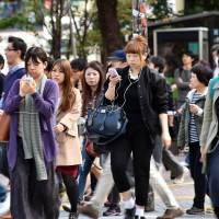 Smartphone in hand, pedestrians cross a busy Tokyo street on Nov. 3. | AFP-JIJI