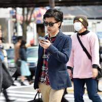 A pedestrian looks at his smartphone on a Tokyo street. With over half of all Japanese now owning the devices, the potential for accidents on the nation's streets has soared.  | AFP-JIJI