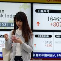 A pedestrian walks past an electronic display showing the jump in the Nikkei 225 stock index outside a securities firm in Tokyo on Friday. | BLOOMBERG