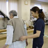 A physical therapist (right) helps a patient at Jukoukai Hospital in Tokyo in September. Prime Minister Shinzo Abe's decision to postpone a second sales-tax increase may result in cuts to hospital expenses designed to slow the nation's spiraling health care costs. | BLOOMBERG