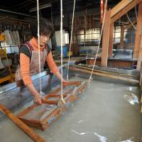 Craftswoman Hisako Uchimura sieves raw materials for the 'hosokawa-shi' variety of washi paper using a screen in her studio in Higashi-Chichibu, Saitama Prefecture, on a recent fall day. | YOSHIAKI MIURA
