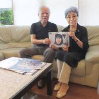 Shigeru and Sakie Yokota hold a portrait of their daughter Megumi after an interview in Kawasaki on July 16. | BLOOMBERG