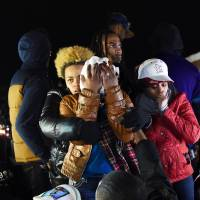 No surprise: Michael Brown's mother, Leslie McSpadden, covers her face as she and other protesters react to the grand jury decision on Nov. 24 not to press charges against police officer Darren Wilson for the fatal shooting of her son in Ferguson, Missouri. | AFP-JIJI