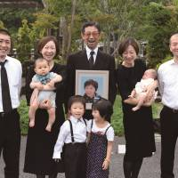 Family affairs: A still from 'Umareru Zutto Issho,' showing Kenzo Kon (center) holding a picture of his deceased wife, surrounded by his daughters, sons in law and grandchildren.© IndigoFilms, Inc.