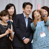 Center of attention: Prime Minister Shinzo Abe poses for a selfie at the 19th International Conference for Women in Business in Tokyo in July. | KYODO