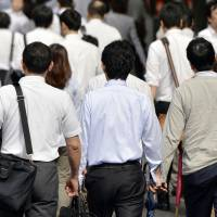 Morning march: Japanese workers make their way through Tokyo during the morning commute. | KYODO