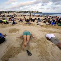 Shore thing: People participate in a protest against Group of 20 nations with poor emissions records by burying their heads in the sand at Sydney's Bondi Beach on Nov. 13. | REUTERS