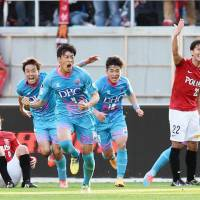 All change: Sagan Tosu's Teruaki Kobayashi (4) leads the celebrations after scoring an injury-time equalizer in Saturday's 1-1 draw with Urawa Reds. | KYODO