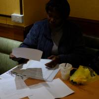 Obueza catches up on paperwork at a cafe. PRAJ recently began printing membership cards for the 590 former detainees it organizes. The cards are meant to serve as an alternate means of identification, and to provide members with immediate access to PRAJ's network of lawyers and advocates. Obueza visits detention centers daily, and is often the only advocate available to Japanese-illiterate detainees seeking legal and moral support.  | DREUX RICHARD