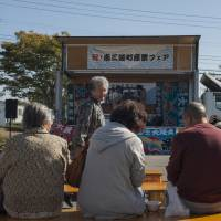 Catching up: Locals listen to live music and taiko drumming at the monthly Fukko Ichi, or Revival Market, in Minamisanriku. | SKYE HOHMANN
