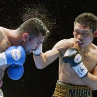 On target: Takashi Miura lands a punch against Mexican challenger Edgar Puerta in the fifth round of Saturday's WBC super featherweight title bout in Yokohama. Miura won by TKO in the sixth round to keep his title belt. | KYODO