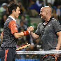 Warm greeting: Kei Nishikori shakes hands with Andre Agassi after their exhibition match on Saturday in Tokyo. Nishikori won the shortened match 8-6.  | AFP-JIJI