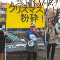 Organizer Katsuhiko Furusawa harangues the crowd, made up mostly of reporters, while standing in front of a banner reading 'Crush Christmas!' on Sunday. | MARK SCHREIBER