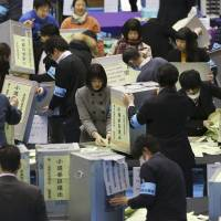 Election staff members open ballot boxes for vote counting in the parliamentary lower house elections at a ballot counting center in Tokyo. | AP