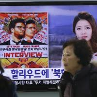 People walk past a TV screen showing a poster of Sony Picture's 'The Interview' in a news report,  at the Seoul Railway Station in South Korea. | AP