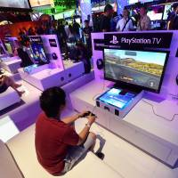 People test the new Playstation TV consoles at the annual E3 video game extravaganza, where game-makers battle for the market share. Online hackers took credit for an online service outage of Sony's PlayStation and Microsoft's Xbox game consoles on Dec. 25, 2014 as people unwrapped their new toys on Christmas morning. | AFP-JIJI
