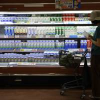 A shopper passes cartons of milk in the dairy section of a Daiei Inc. supermarket in Urayasu, Chiba Prefecture, in August. | BLOOMBERG