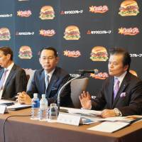 Masato Watanabe (right), president of Carl's Jr. Japan Inc., speaks to reporters in Tokyo as Mitsuuroko Group Holdings Co. CEO Kohei Tajima and Michael Murphy, president of CKE Restaurants Holdings Inc., look on. | KAZUAKI NAGATA