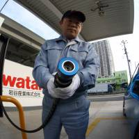 An Iwatani Corp. employee prepares to fill a Toyota Mirai fuel cell vehicle at a hydrogen fueling station in Tokyo on Nov. 17. | BLOOMBERG