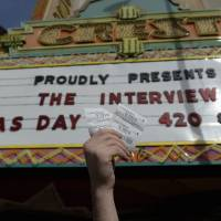 Tickets to 'The Interview' are held up by Crest Theater manager Donald Melancon in Los Angeles on Wednesday. | REUTERS