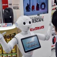 SoftBank's Pepper robot tries to sell Nestle coffee machines at a Bic Camera electronics outlet in Tokyo on Monday. | AFP-JIJI