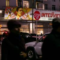 People walk past a banner for 'The Interview' at Arclight Cinemas on Wednesday, in the Hollywood section of Los Angeles. A U.S. official says North Korea perpetrated the unprecedented act of cyberwarfare against Sony Pictures. | AP