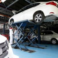 Honda cars are serviced in Petaling Jaya, Malaysia, on Monday. The president of embattled auto parts manufacturer Takata stepped down on Wednesday amid the recall of millions of vehicles equipped with its air bags. | AP