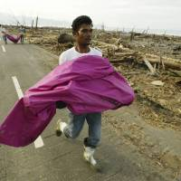 Residents of Leupung in Indonesia's Aceh province carry victims of the Dec. 26, 2004, tsunami, which was triggered by a magnitude-9.1 quake, to a freshly dug grave on Jan. 27, 2005.   REUTERS