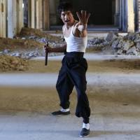Abbas Alizada, who calls himself the 'Afghan Bruce Lee,' poses for the media in Kabul on Tuesday. From the ruins of an iconic bombed-out palace above Kabul, the young man bearing a striking resemblance to the kung fu legend is high-kicking his way to Internet fame, aiming to show another side to his war-weary nation. | REUTERS