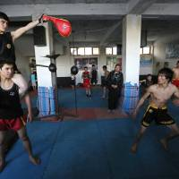 Abbas Alizada, who calls himself the Afghan Bruce Lee, works out during a media event in Kabul on Tuesday. From the ruins of an iconic bombed-out palace above Kabul, the young man bearing a striking resemblance to the kung fu legend is high-kicking his way to Internet fame, aiming to show another side to his war-weary nation. | REUTERS
