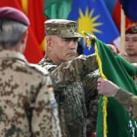 U.S. Gen. John Campbell, commander of the NATO-led International Security Assistance Force, folds the flag of the ISAF during the change of mission ceremony in Kabul on Sunday, when the American-led coalition officially ended its combat mission after a more than 13 year war that ousted the Taliban government in 2001. | REUTERS