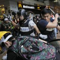 Police officers beat pro-democracy protesters outside government headquarters in Hong Kong on Monday. | AP