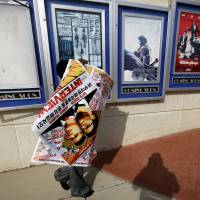 A poster for the movie 'The Interview' is carried away by a worker after being pulled from a display case at a Carmike Cinemas movie theater Wednesday in Atlanta. Georgia-based Carmike Cinemas has decided to cancel its planned showings of 'The Interview' in the wake of threats against theatergoers by the Sony hackers. | AP