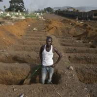 A grave digger prepares new graves at a cemetery in Freetown, Sierra Leone, on Sunday. About 40 suspected Ebola victims are being buried in this cemetery every day as the country continues to fight the epidemic. | REUTERS