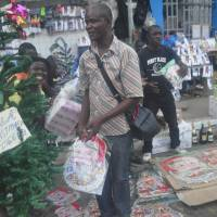 Liberians shop for a Christmas tree in Monrovia on Wednesday. Authorities this year have banned any activities that could further the spread of the highly contagious virus, which has killed more than 7,000 people in West Africa over the past year. | AP