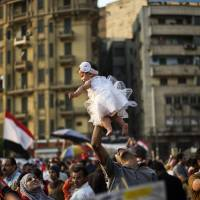 An Egyptian man holds his daughter aloft in Cairo's Tahrir Square in July 2013. A deadly police crackdown on supporters of the Muslim Brotherhood and a web of 'citizen informants' have generated a climate of fear in public places, with Egyptians becoming increasingly wary of airing views critical of President Abdel-Fattah el-Sissi's regime. | AFP-JIJI