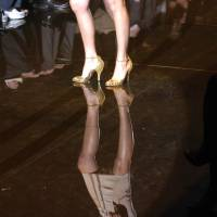 A model's reflection is seen on the catwalk at a Gucci fashion show in Milan, Italy. A new French study has shown that men behave very differently toward women in high heels. | BLOOMBERG