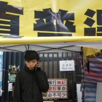 Student protest leader Joshua Wong talks on his phone during his hunger strike at the area occupied by pro-democracy demonstrators outside government headquarters in Hong Kong on Tuesday. The yellow banner above him reads 'Genuine universal suffrage.' | AP