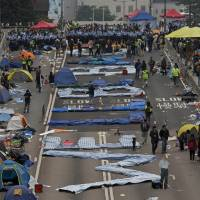 'We'll be back,' Hong Kong protesters chant as main camp site dismantled